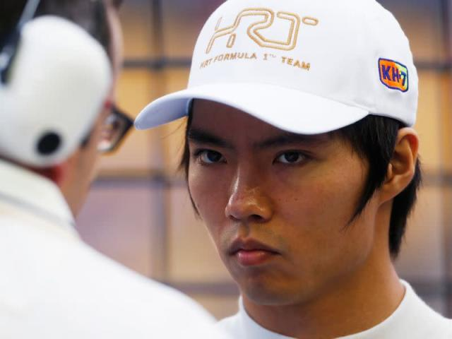 HRT Formula One driver Ma of China talks to a crew member during the first practice session of the Singapore F1 Grand Prix