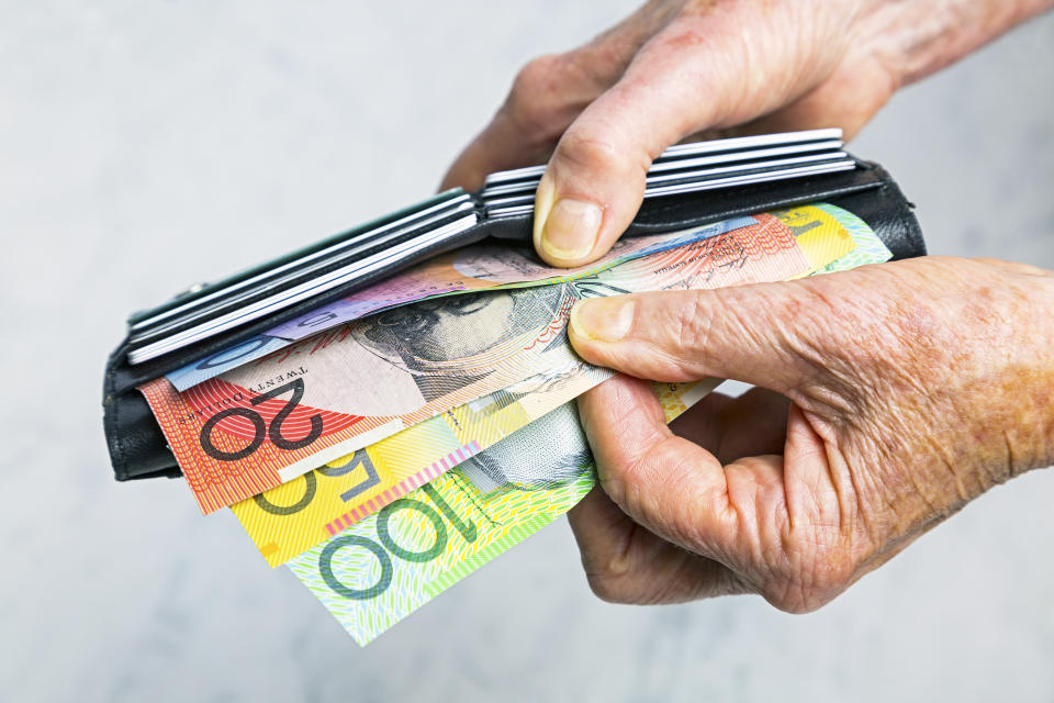 Close-up, senior female hands taking Australian banknotes (cash, currency) from purse containing many credit cards.  Horizontal, studio, copy space.