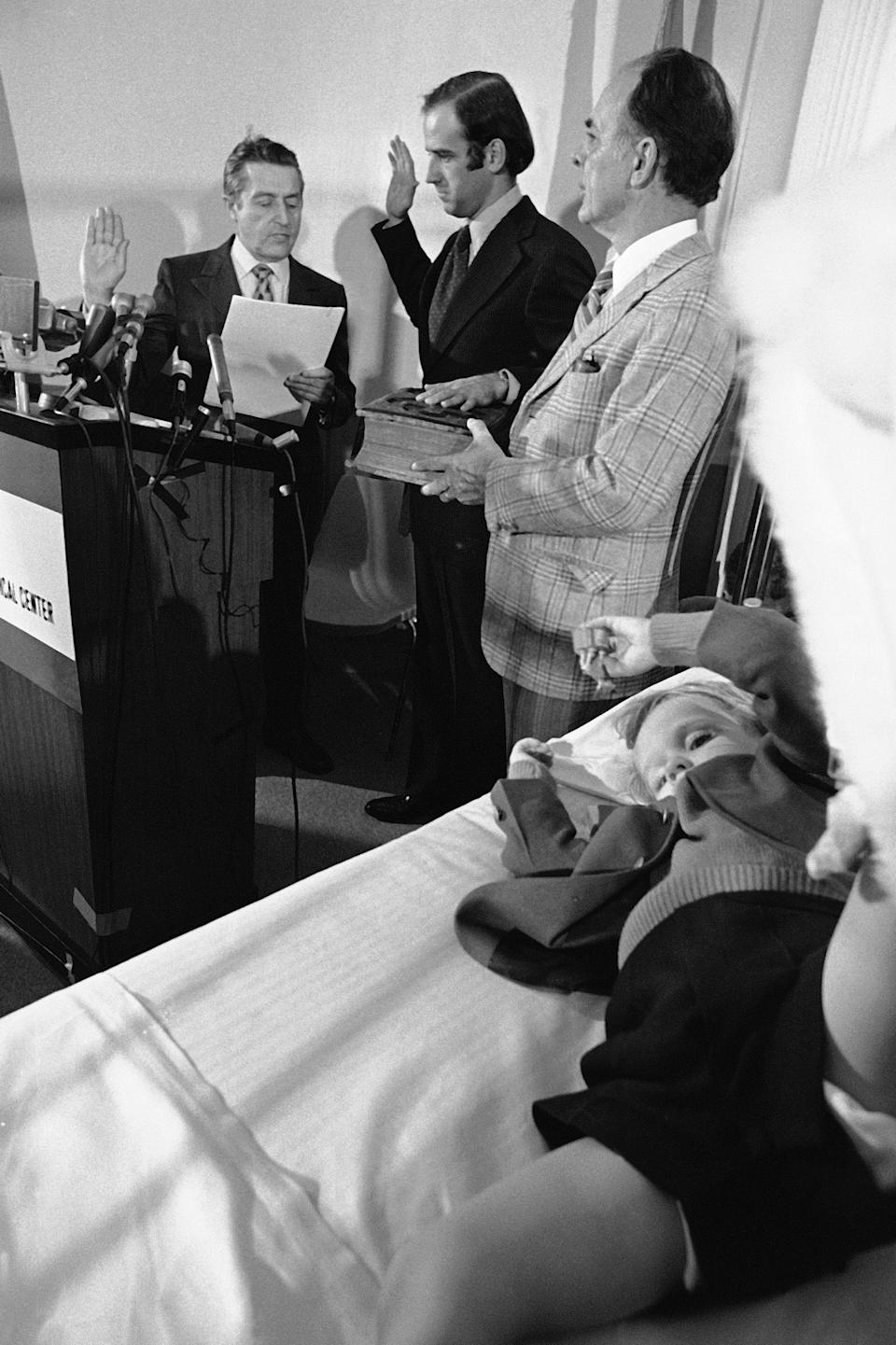 In this Jan. 5, 1973 file photo, 4-year-old Beau Biden, foreground, watches his dad, Joe Biden, being sworn in as the U.S. senator from Delaware, in a Wilmington hospital. Beau was injured in an accident that killed his mother and sister in December. (AP Photo/File)