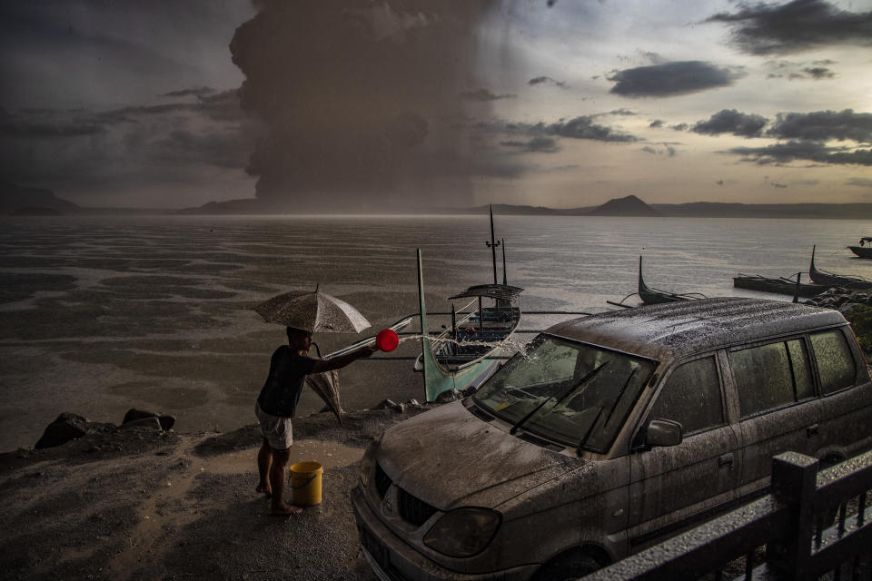 In this image released by World Press Photo, Thursday April 15, 2021, by Ezra Acayan for Getty Images, part of a series titled Taal Volcano Eruption, which won second prize in the Nature Stories category, shows A resident of Talisay in Batangas washes down a car, which is covered in volcanic ash mixed with rain, as Taal Volcano erupts, Batangas, Philippines, on Jan. 12, 2020. (Ezra Acayan for Getty Images, World Press Photo via AP)