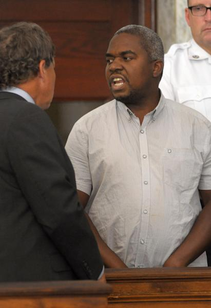 Ernest Wallace, of Miramar, Fla., center, mouths words to people sitting in Attleboro District Court, in Attleboro, Mass., while standing next to his attorney David Meier, left, during his arraignment, Monday, July 8, 2013. Wallace, who pleaded not guilty, is facing an accessory to murder charge in the case involving former New England Patriots tight end Aaron Hernandez and has been ordered held without bail. (AP Photo/Mark Stockwell, Pool)