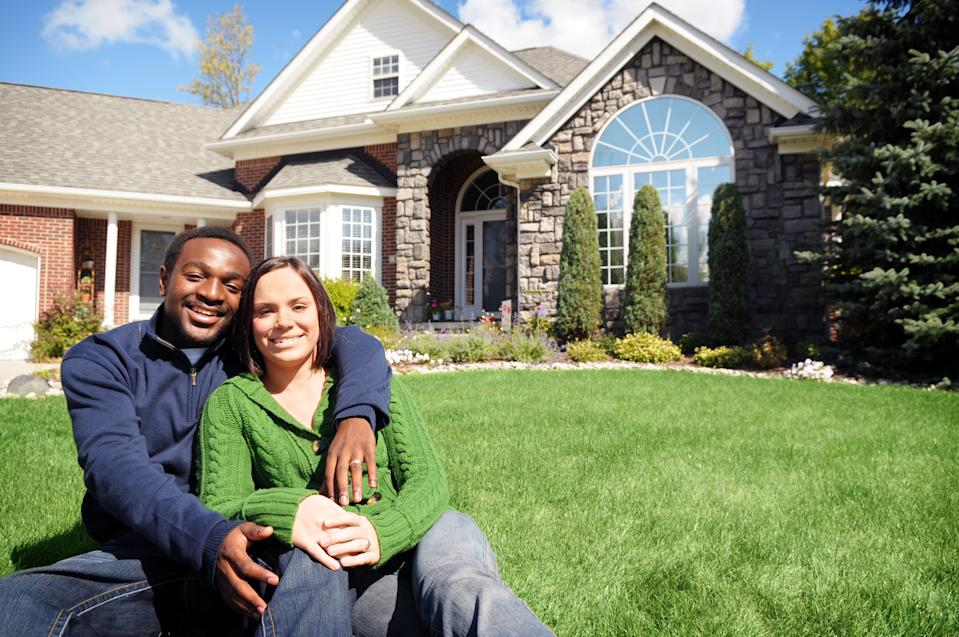 Color photo of a happy, young couple sitting in front of a new home.