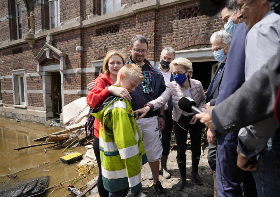 European Commission President Ursula von der Leyen, center, speaks with Madeline Brasseur, 37, Paul Brasseur, 42, and their son Samuel, 12 as she tours the village after flooding in Pepinster, Belgium, Saturday, July 17, 2021. Residents in several provinces were cleaning up after severe flooding in Germany and Belgium turned streams and streets into raging torrents that swept away cars and caused houses to collapse. (AP Photo/Virginia Mayo)