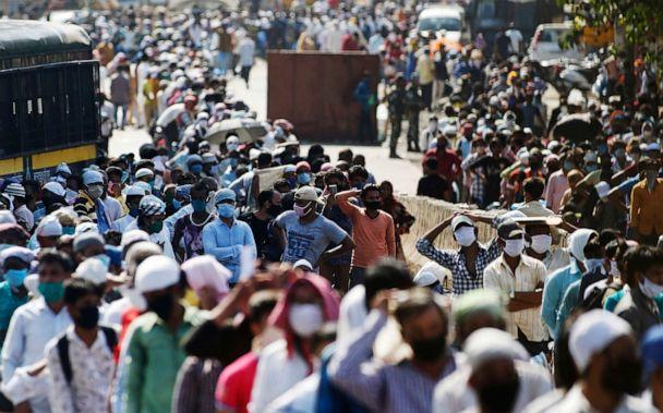 PHOTO: Migrant workers gather for transport to the railway station for their onward journey to their home states, at Dharavi slum in Mumbai, India, on May 26, 2020. (Rajanish Kakade/AP)