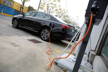 A Roewe 950 hybrid electric car is displayed with its plug-in charger at an electric car dealership in Shanghai
