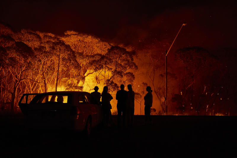 LAKE TABOURIE, AUSTRALIA - JANUARY 04: Residents look on as flames burn through bush on January 04, 2020 in Lake Tabourie, Australia. A state of emergency has been declared across NSW with dangerous fire conditions forecast for Saturday, as more than 140 bushfires continue to burn. There have been eight confirmed deaths in NSW since Monday 30 December. 1365 homes have been lost, while 3.6 million hectares have been burnt this fire season. (Photo by Brett Hemmings/Getty Images)