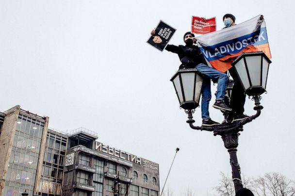 PHOTO: Young protesters hold banners as climnb atop a lamppost in Pushkin Square, Moscow,  Jan. 23, 2021. (Getty Images)