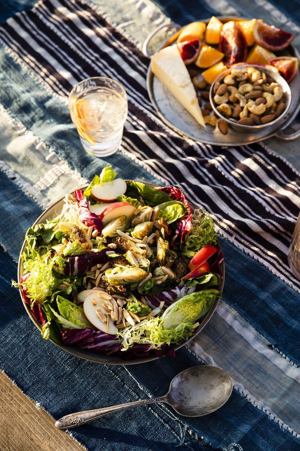 "<p>This may be the ultimate Thanksgiving salad. Crispy roasted sprouts combine with mixed lettuce, crunchy apples, toasted almonds, and nutty asiago cheese, all topped with a sweet vinaigrette. Trust us, the bowl will quickly get emptied.</p><p><strong><a href=""https://www.countryliving.com/food-drinks/a34276952/crispy-brussels-sprouts-salad/"" rel=""nofollow noopener"" target=""_blank"" data-ylk=""slk:Get the recipe"" class=""link rapid-noclick-resp"">Get the recipe</a>.</strong></p><p><a class=""link rapid-noclick-resp"" href=""https://www.amazon.com/Gibson-60687-03-Laroda-Including-Acacia/dp/B0088D4N7M?tag=syn-yahoo-20&ascsubtag=%5Bartid%7C10050.g.4710%5Bsrc%7Cyahoo-us"" rel=""nofollow noopener"" target=""_blank"" data-ylk=""slk:SHOP SALAD BOWLS"">SHOP SALAD BOWLS</a></p>"