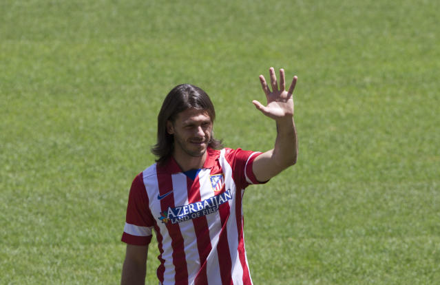 Martin Demichelis of Argentina waves during his presentation at the Vicente Calderon stadium after signing for Atletico Madrid, Madrid, Spain, Friday, July 12, 2013. The 32-year-old Demichelis, an Argentine international, who spent the past two and a half seasons with Malaga, has signed a one-year contract with Atletico. (AP Photo/Paul White)
