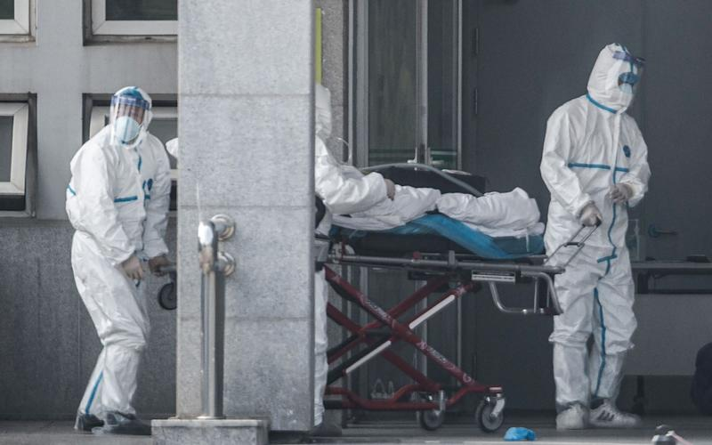 Medical staff members carry a patient into the Jinyintan hospital, where patients infected by a mysterious Sars-like virus are being treated - AFP