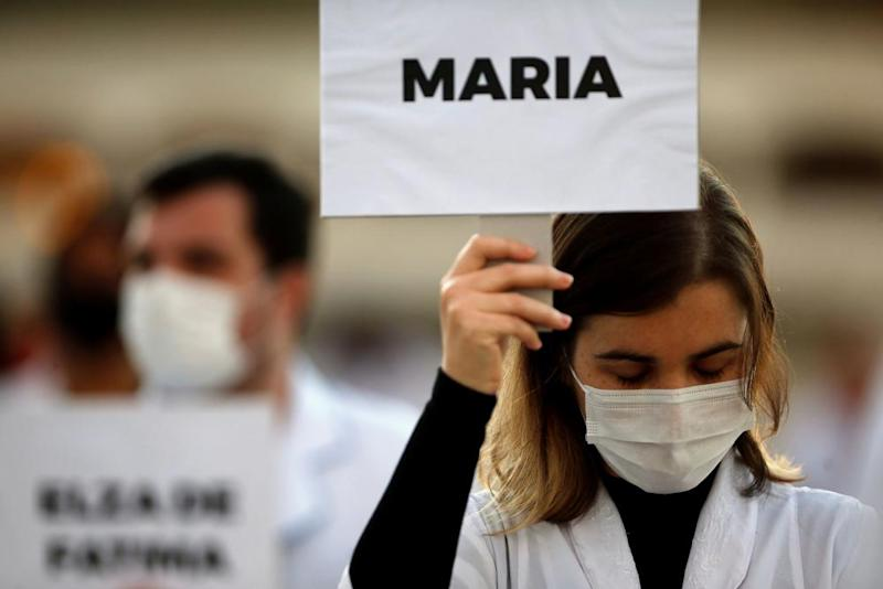 Nurses with signs bearing the names of the healthcare professionals who have died from coronavirus hold a demonstration in Brasilia.