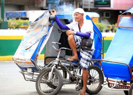 Tricycle taxi driver smokes cigarette while taking a break along a main street in metro Manila