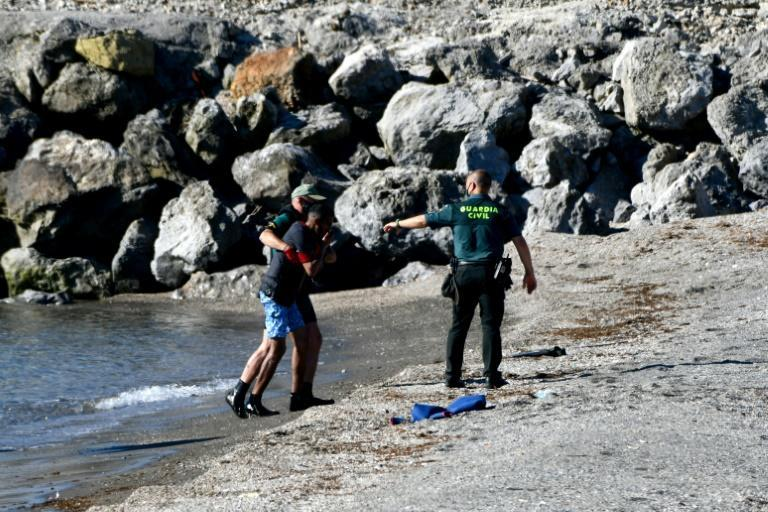 Spanish Civil guards help a migrant after he arrived swimming to the Spanish enclave of Ceuta from neighbouring Morocco on May 17, 2021