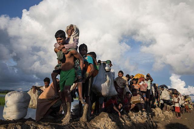 <p>Thousands of Rohingya refugees fleeing from Myanmar walk along a muddy rice field after crossing the border in Palang Khali, Cox's Bazar, Bangladesh, on October 9, 2017. Well over a half a million Rohingya refugees have fled into Bangladesh since late August during the outbreak of violence in Rakhine state causing a humanitarian crisis in the region with continued challenges for aid agencies. (Photograph by Paula Bronstein/Getty Images) </p>