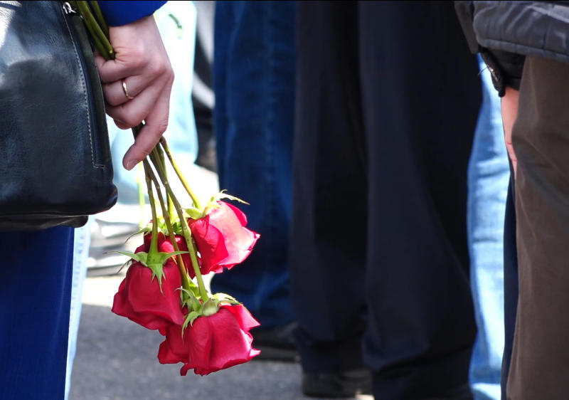 """In this grab taken from a footage provided by the Russian State Atomic Energy Corporation ROSATOM press service, a woman holds roses as she and other people gather for the funerals of five Russian nuclear engineers killed by a rocket explosion in Sarov, the closed city, located 370 kilometers (230 miles) east of Moscow, which has served as a base for Russia's nuclear weapons program since the late 1940s, Russia, Monday, Aug. 12, 2019. Russia's Rosatom state nuclear concern said Thursday's explosion at a military testing range in northwestern Russia occurred while the engineers were testing a """"nuclear isotope power source"""" for a rocket engine, a tragedy that fueled radiation fears and raised new questions about a secretive weapons program (Russian State Atomic Energy Corporation ROSATOM via AP)"""