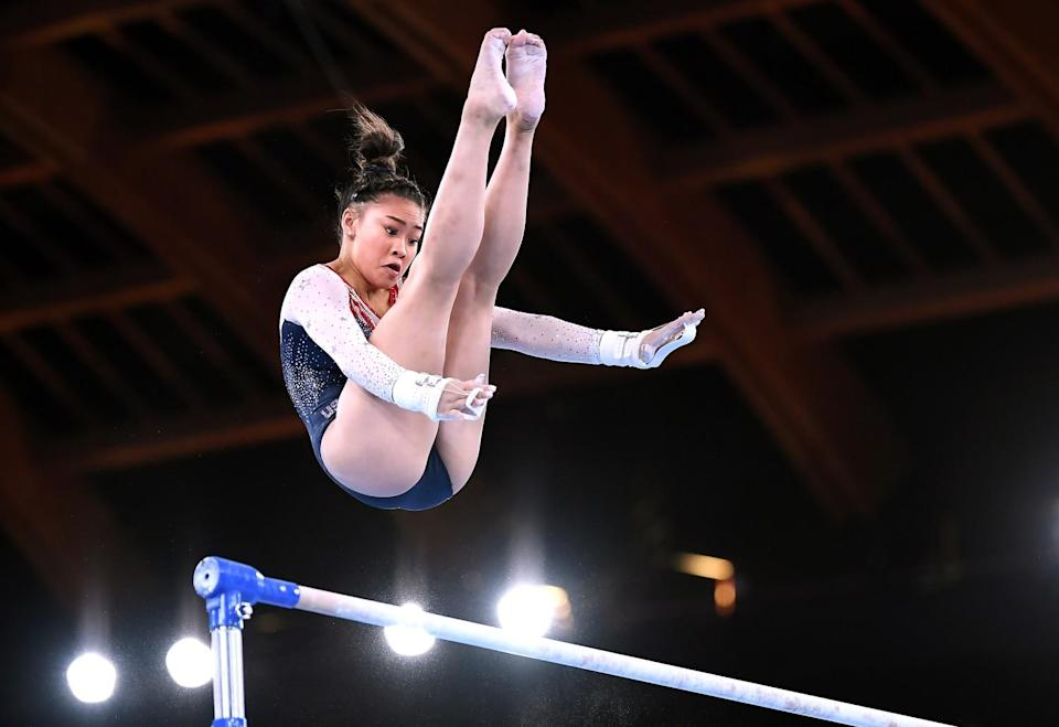 Sunisa Lee hovers above the uneven bars.