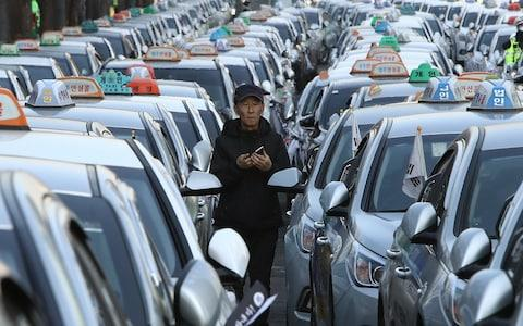 A taxi driver stands amid parked taxis at a rally - Credit: Chung Sung-Jun/Getty