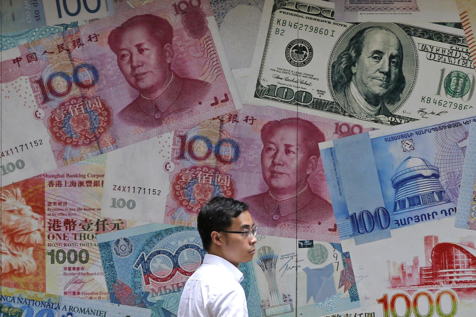 FILE - In this June 10, 2019, file photo, a man walks past a money exchange shop decorated with different banknotes at Central, a business district of Hong Kong. China's yuan fell Friday, Aug. 2, 2019, to its lowest level of the year against the dollar following U.S. President Donald Trump's threat of new tariffs on Chinese goods, coming close to breaking the politically sensitive level of seven to the U.S. currency. (AP Photo/Kin Cheung, File)