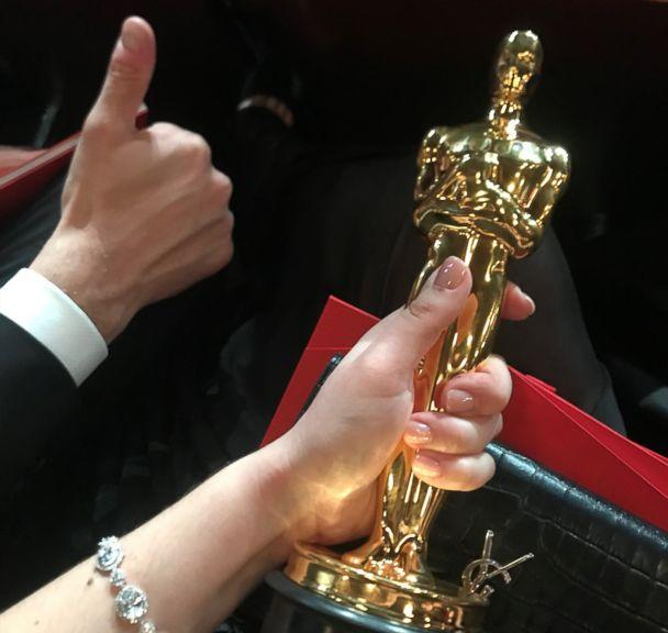 PHOTO: Rayka Zehtabchi and Sam Davis hold their Oscar inside the Dolby Theatre. (Netflix)