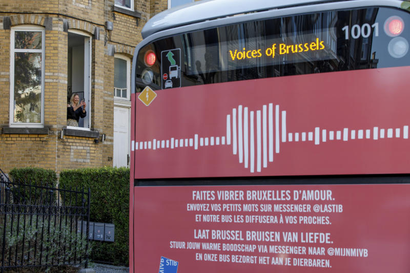 A woman takes a mobile phone photo of a bus delivering a loudspeaker message from family and friends in Brussels, Wednesday, April 22, 2020. With streets in the Brussels capital mostly devoid of loud traffic and honking horns, a simple piece of emotional poetry can split the air. The public bus company, STIB-MIVB, has been calling on people to send in voice messages, which are now delivered by a special bus driving in a loop to connect all the messages and leave a trail of happiness. (AP Photo/Olivier Matthys)
