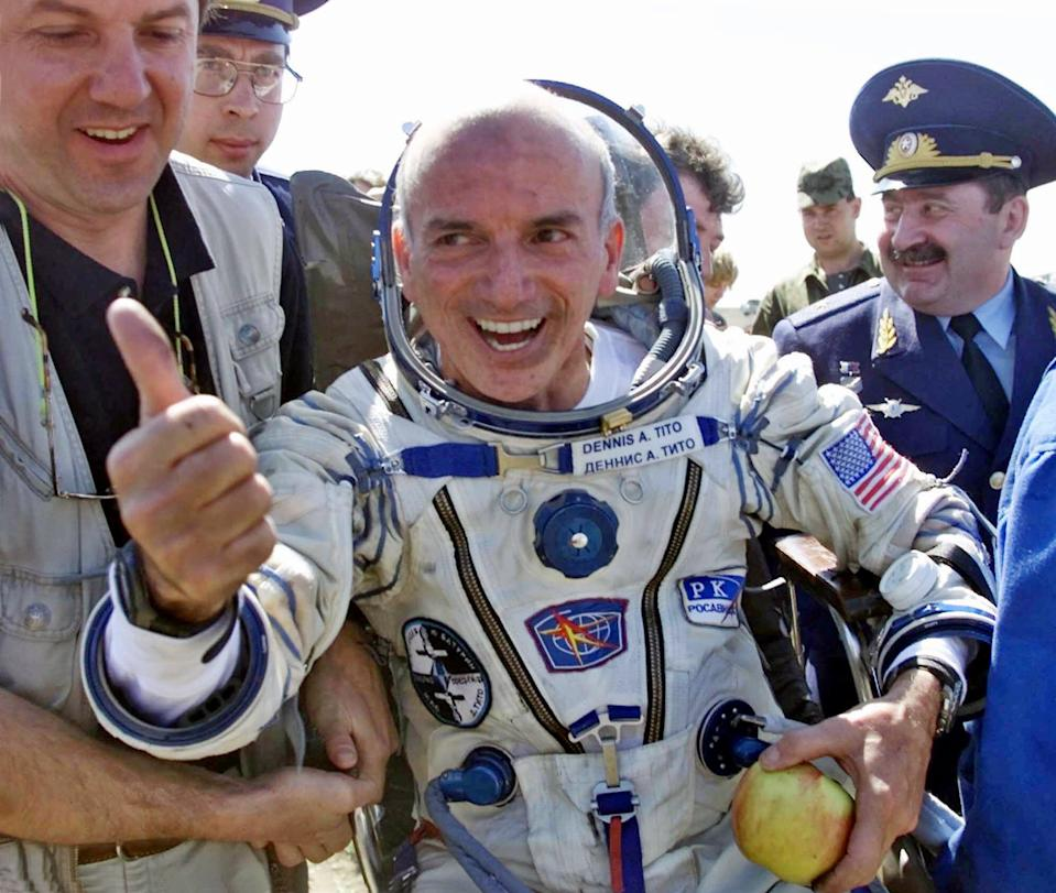 American multimillionaire  Dennis Tito, 60, gestures shortly after his landing on the steppes, 80 kilometers (50 miles) northeast of Arkalyk, Kazakstan, Sunday, May 6, 2001. Others are unidentified. The Russian Soyuz capsule carrying the world's first paying space tourist landed successfully on Sunday, ending Tito's multimillion dollar cosmos adventure. (AP Photo/Mikhail Metzel)