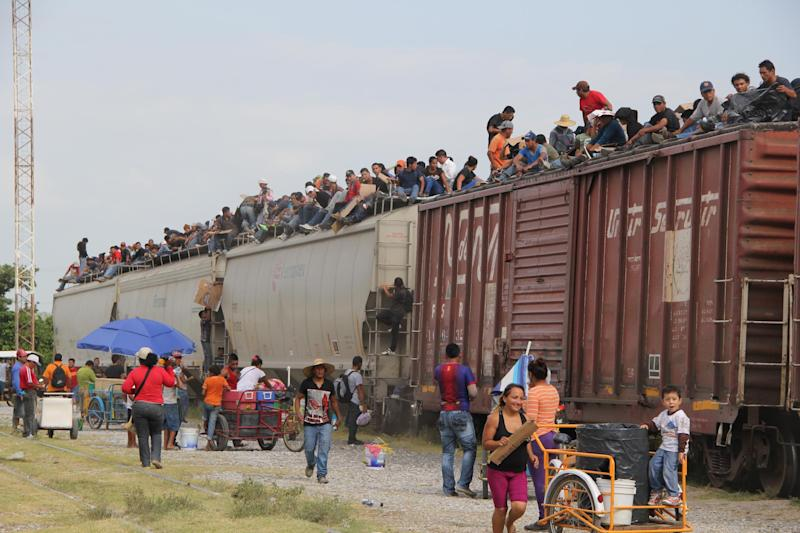 Central American immigrants get on the so-called La Bestia (The Beast) cargo train, in an attempt to reach the Mexico-US border, in Arriaga, Chiapas state, Mexico on July 16, 2014 (AFP Photo/Elizabeth Ruiz)