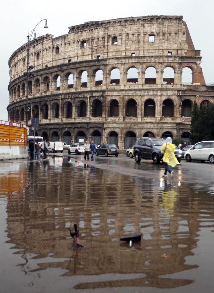 "People walk past a paddle next to Rome's ancient Colosseum, Thursday, Oct. 20, 2011. A torrential rainstorm battered Rome during the morning rush hour Thursday, causing flash floods that killed one man, felled trees and blocked thousands of commuters from reaching their workplaces. Police rescued dozens of people from low-lying buildings. In foreground is seen a bicycle covered by water. Additional images featured in <a href=""http://news.yahoo.com/photos/torrential-rainstorm-floods-rome-1319122740-slideshow/"">Yahoo! News</a>. (AP Photo/Pier Paolo Cito)"