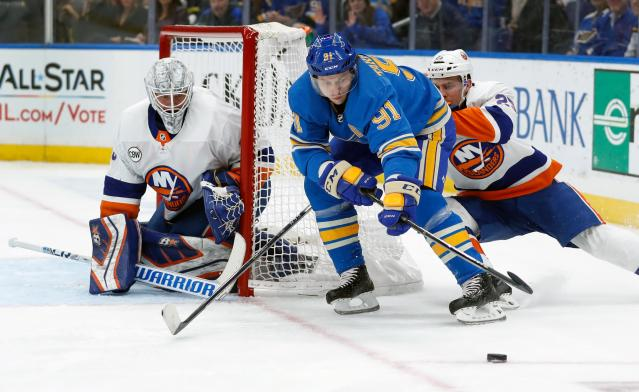 St. Louis Blues' Vladimir Tarasenko (91), of Russia, reaches for the puck as New York Islanders goaltender Robin Lehner, of Sweden, and Devon Toews, right, defend during the second period of an NHL hockey game Saturday, Jan. 5, 2019, in St. Louis. (AP Photo/Jeff Roberson)