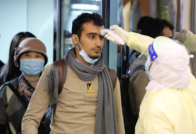 Passengers coming from China wearing masks to prevent a new coronavirus are checked by Saudi Health Ministry employees upon their arrival at King Khalid International Airport, in Riyadh, Saudi Arabia January 29, 2020. REUTERS/Ahmed Yosri