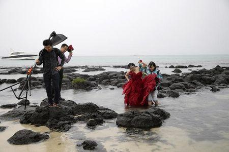 A Chinese couple from Yunnan accompany a photographer as they make their way through the water and on the rocks for a wedding photo session at the Cap Malheureux beach on the Indian Ocean island Mauritius