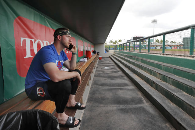 Minnesota Twins catcher Mitch Garver talks on his phone in an empty dugout at Hammond Stadium, Thursday, March 12, 2020, in Fort Myers, Fla. Major League Baseball has suspended the rest of its spring training game schedule because if the coronavirus outbreak. The league is also delaying the start of its regular season by at least two weeks. (AP Photo/Elise Amendola)