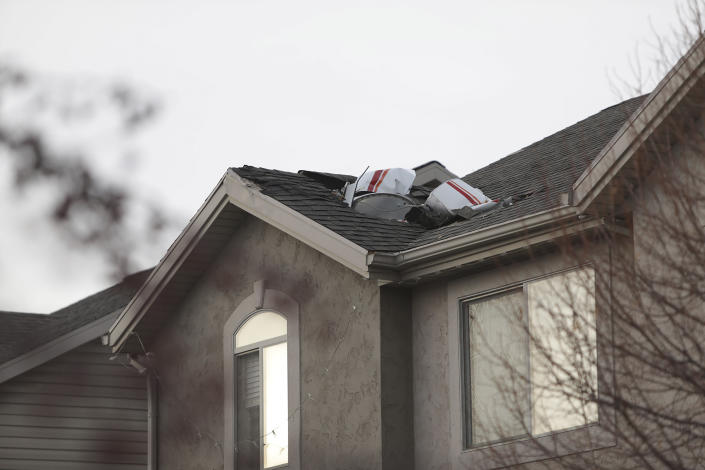 Debris from a small private plane that crashed in a residential area is shown on a roof Wednesday, Jan. 15, 2020, in Roy, Utah. The small plane crashed Wednesday, killing the pilot as the aircraft narrowly avoided hitting any townhomes, authorities said. (Ben Dorger/Standard-Examiner, via AP)