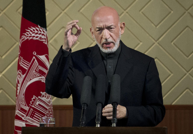 "Afghan President Hamid Karzai gestures during a ceremony at Kabul University in Kabul, Afghanistan, Thursday, May 9, 2013. Karzai said he is ready to let the U.S. have nine bases in the country after the 2014 combat troop pullout, but wants Washington's ""security and economic guarantees"" first.  (AP Photo/Anja Niedringhaus)"