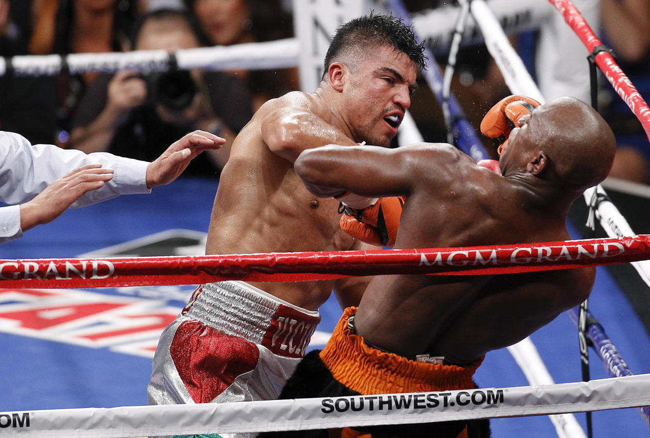 Floyd Mayweather rears back on the ropes after a head butt by Victor Ortiz, left, in the fourth round during their WBC welterweight title fight, Saturday, Sept. 17, 2011, in Las Vegas. Mayweather won by knockout in the fourth round. (AP Photo/Eric Jamison)