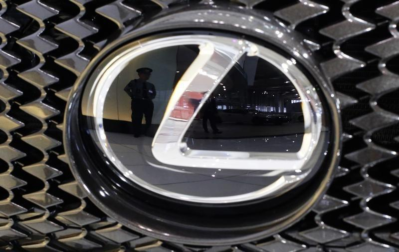 A security guard is reflected in the logo of a Toyota Motor Corp's Lexus car at the company's showroom in Tokyo