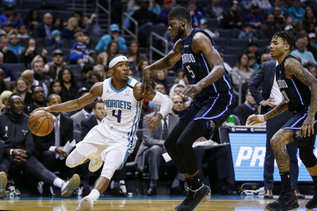 Charlotte Hornets guard Devonte' Graham, left, drives around Orlando Magic center Mo Bamba as Orlando Magic guard Markelle Fultz looks on in the first half of an NBA basketball game in Charlotte, N.C., Monday, Jan. 20, 2020. (AP Photo/Nell Redmond)