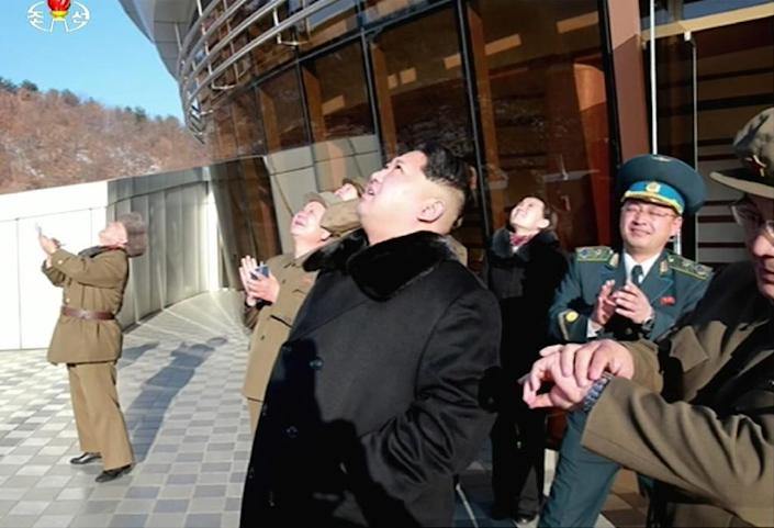 Picture taken from North Korean TV and released by South Korean news agency Yonhap shows North Korean leader Kim Jong-Un (C) looking at the rocket launch (AFP Photo/YONHAP)