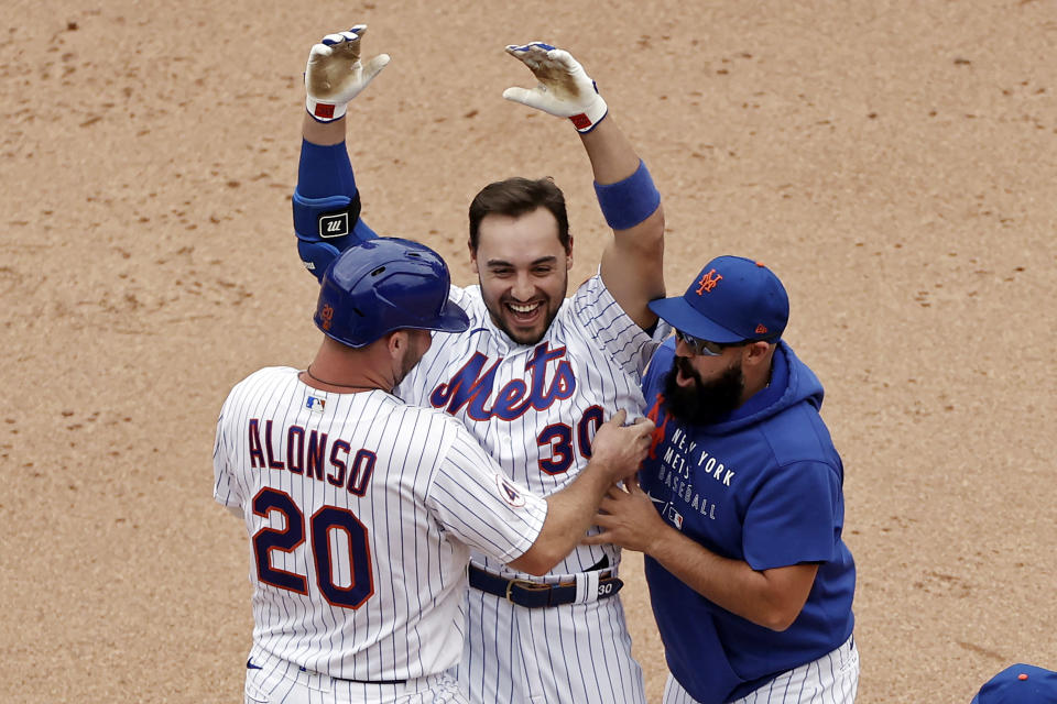New York Mets' Michael Conforto celebrates his walk-off single with Pete Alonso and Luis Guillorme against the Miami Marlins during the ninth inning of the first game of a baseball doubleheader that started April 11 and was suspended because of rain, Tuesday, Aug. 31, 2021, in New York. The Mets won 6-5. (AP Photo/Adam Hunger)