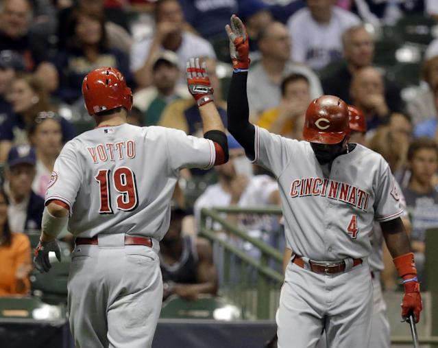 Cincinnati Reds' Joey Votto (19) is congratulated by Brandon Phillips after Votto hit a home run during the sixth inning of a baseball game against the Milwaukee Brewers on Thursday, Aug. 15, 2013, in Milwaukee. (AP Photo/Morry Gash)
