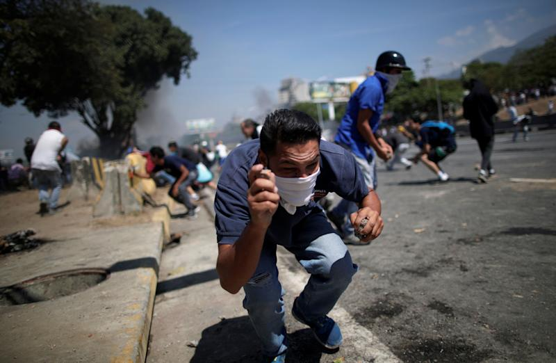 "An opposition demonstrator crouches down, holding rocks, on a street near the Generalisimo Francisco de Miranda Airbase ""La Carlota"" in Caracas, Venezuela April 30, 2019. (Photo: Ueslei Marcelino/Reuters)"
