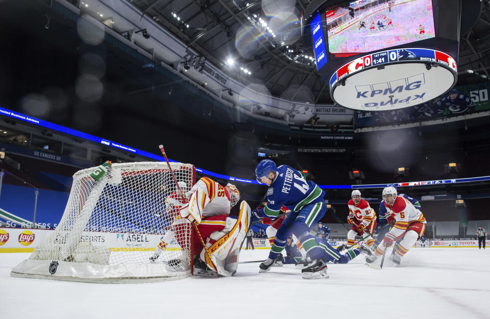 Calgary Flames goalie Jacob Markstrom (25) stops Vancouver Canucks' Elias Pettersson (40) during the first period of an NHL hockey game Saturday, Feb. 13, 2021, in Vancouver, British Columbia. (Darryl Dyck/The Canadian Press via AP)