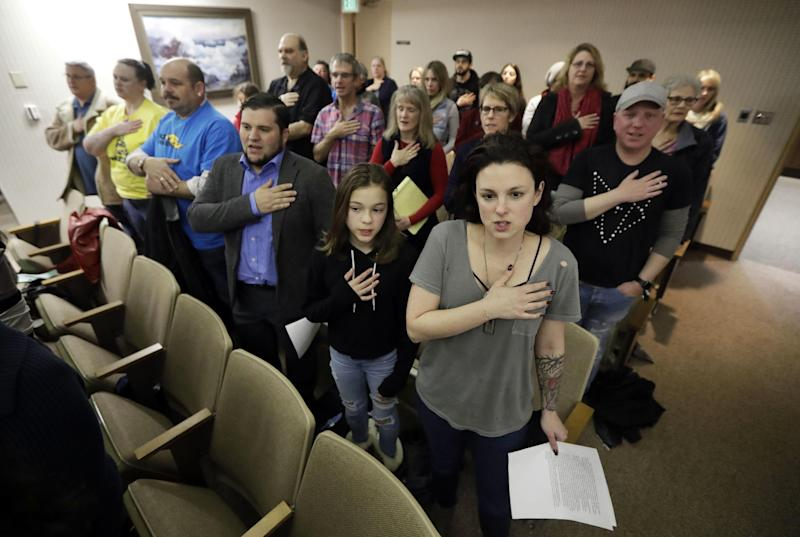 Members of the Orchard City Indivisible Group recite the pledge of allegiance during a city council meeting where they would speak against the policies of President Trump Tuesday, March 7, 2017, in Campbell, Calif. Old-school, anti-capitalist activists and new-school, free-enterprise techies are pushing aside their differences to take on a common foe. (AP Photo/Marcio Jose Sanchez)