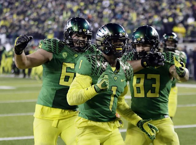 Oregon receiver Josh Huff, middle, celebrates scoring the winning touchdown with less than a minute to go with teammates Tyler Johnstone, left, and Johnny Mundt during the second half of an NCAA college football game against Oregon State in Eugene, Ore., Friday, Nov. 29, 2013. Oregon won 36-35. (AP Photo/Don Ryan)