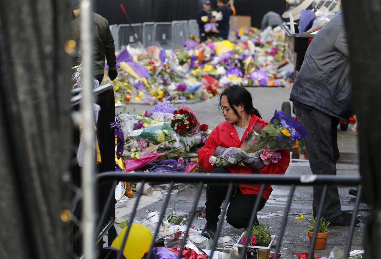 A workers picks up flowers amid thousands of items left in honor of Kobe Bryant, including hundreds of basketballs, from Chick Hearn Court from Staples Center, home of the Los Angeles Lakers, early Monday, Feb. 3, 2020, in Los Angeles. Mourners left the items after the death of the former Lakers legend, his daughter and seven others, in a helicopter crash one week ago.(AP Photo/Reed Saxon)
