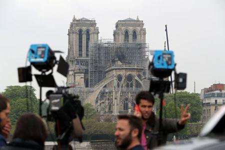 Members of the media work on a bridge after a massive fire devastated large parts of Notre-Dame Cathedral in Paris
