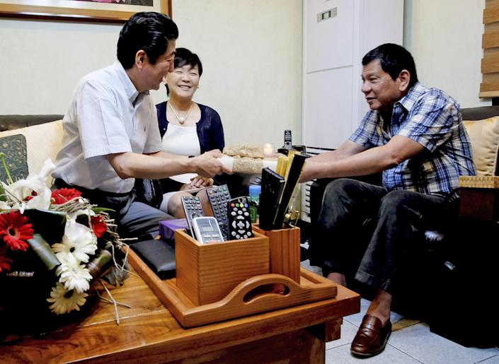 In this photo provided by the Presidential Photographers Division Malacanang Palace, Philippine President Rodrigo Duterte, right, hands a gift to visiting Japanese Prime Minister Shinzo Abe and his wife Akie to the President's residence at Dona Luisa Village in Davao City, Friday, Jan. 13, 2017, in the southern Philippines. Abe capped his two-day official visit to the Philippines by having breakfast with Duterte at his home in Davao city. (Rene Lumawag, Presidential Photographers' Division via AP)