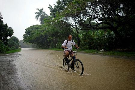 A man rides a bicycle down a flooded road as Subtropical Storm Alberto passes by the west coast of Cuba, in Bahia Honda, Cuba, May 26, 2018.  REUTERS/Alexandre Meneghini