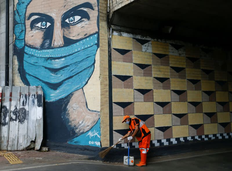 FILE PHOTO: A worker wearing a protective face mask sweeps the street near a mural promoting awareness of the coronavirus disease (COVID-19) outbreak in Jakarta