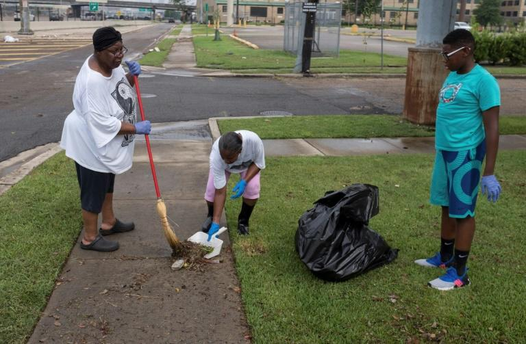 New Orleans residents clean up debris in their yard after flash floods struck the area early on July 10 (AFP Photo/Seth HERALD)