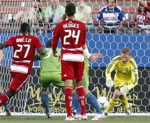 FC Dallas' James Marcelin (27), Matt Hedges (24) and Seattle Sounders' Brad Evans (3) watch as goalkeeper Bryan Meredith (35) leaps forward to make a stop in the first half of an MLS soccer game, Wednesday, May 9, 2012, in Frisco, Texas. (AP Photo/Tony Gutierrez